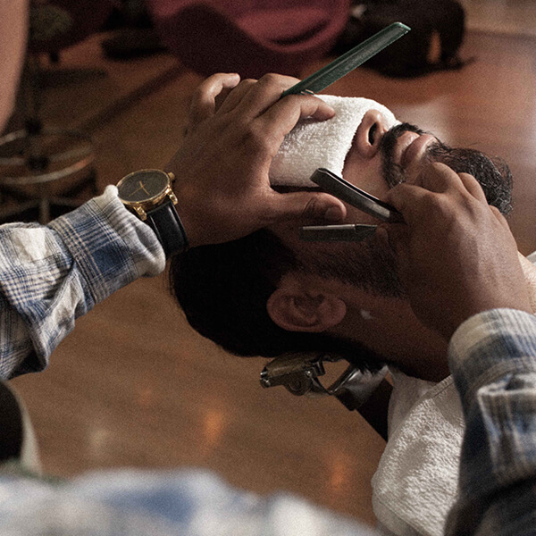 Cliente recebendo corte de barba no Kbloo Barber Shop.